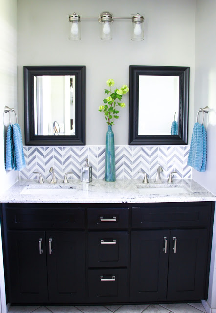 Bathroom remodel with herringbone carrera look tile, chevron marble tile and raised white subway tile